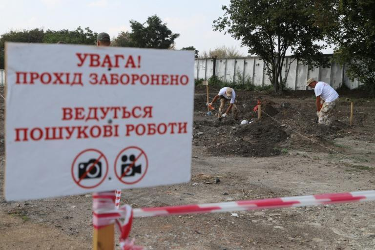 People work on the site of mass graves site unearthed near Odessa airport in Ukraine (AFP/Oleksandr GIMANOV)
