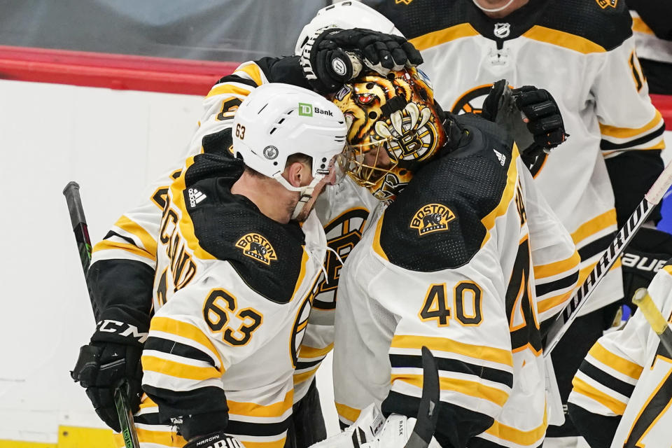 Boston Bruins center Brad Marchand, left, celebrates with goaltender Tuukka Rask (40) after scoring the winning goal in overtime of Game 2 of an NHL hockey Stanley Cup first-round playoff series against the Washington Capitals, Monday, May 17, 2021, in Washington. The Bruins won 4-3. (AP Photo/Alex Brandon)