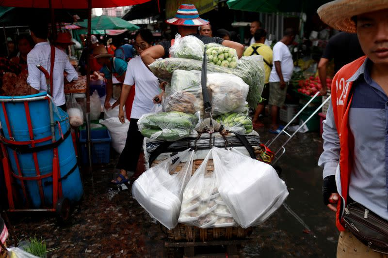 FILE PHOTO: Vegetables are carried in plastics bags at a market in Bangkok