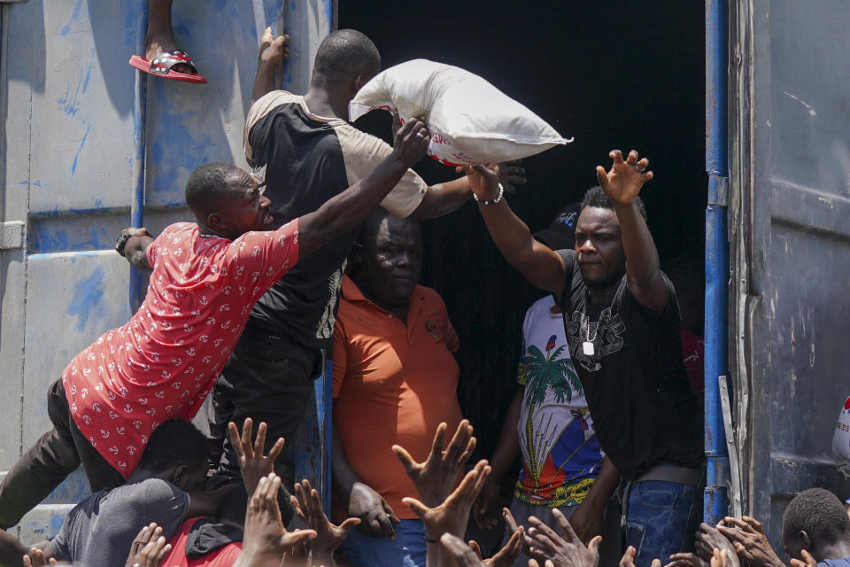 A man tosses out a bag of rice from the trailer of a truck filled with relief supplies, overtaken by residents in Vye Terre, Haiti, Friday, Aug. 20, 2021. Private aid and shipments from the U.S. government and others were arriving in the country's southwestern peninsula that was struck by a 7.2 magnitude quake on Aug. 14. (AP Photo/Fernando Llano)