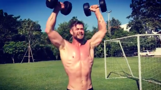 A photo of Chris Hemsworth shirtless lifting weights.