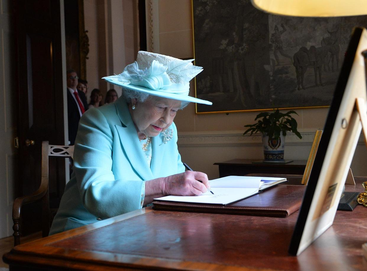 BELFAST, NORTHERN IRELAND - JUNE 25:  (EDITORIAL USE ONLY, NO SALES) In this handout image provided by Harrison Photography, Queen Elizabeth II signs the visitors book at Hillsborough castle as they leave for their final engagement in Coleraine on June 25, 2014 in Belfast, Northern Ireland. The Royal party are visiting Northern Ireland for three days.  (Photo byAaron McCracken/Harrison Photography via Getty Images)