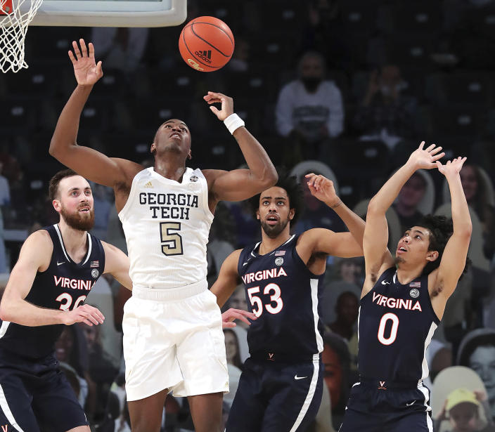 Georgia Tech's Moses Wright and Virginia's Jay Huff, Thomas Woldetensae and Kihei Clark, from left, look for a rebound during an NCAA college basketball game Wednesday, Feb. 10, 2021, in Atlanta. (Curtis Compton/Atlanta Journal-Constitution via AP)