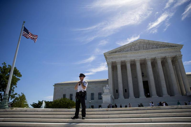 A police officer is seen outside the US Supreme Court after it was announced that the court will allow a limited version of President Donald Trump's travel ban to take effect: Eric Thayer/Getty Images