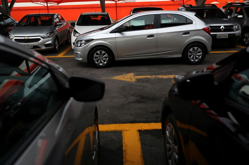 A man drives a Chevrolet Onix hatchback at the car park of a newly opened Movida car rental service store specialized in ride-hailing companies in Sao Caetano do Sul