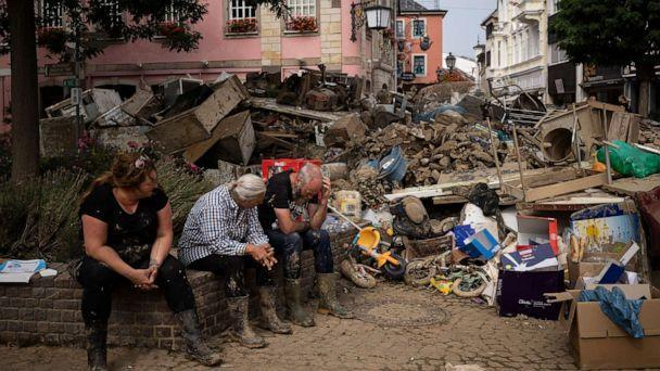 PHOTO: People rest from cleaning up the debris of the flood disaster in Bad Neuenahr-Ahrweiler, Germany, July 19, 2021. (Bram Janssen/AP)