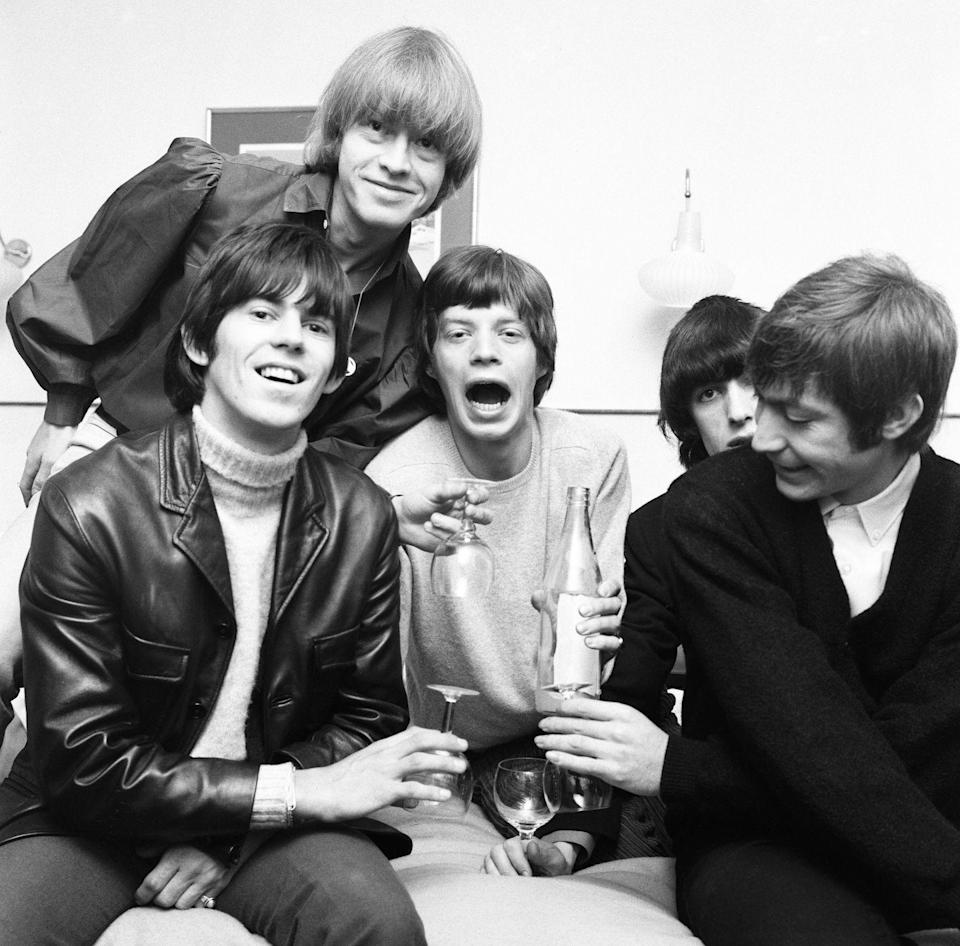 <p>Mick and his Rolling Stones bandmates goof around while making a toast, 1960.</p>