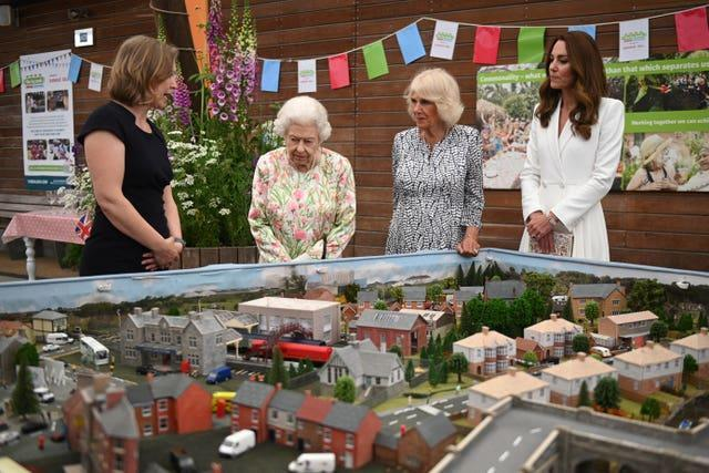 Programme director at the Eden Project, Lindsey Brummitt, shows a scale model of Big Lunch events to the royals