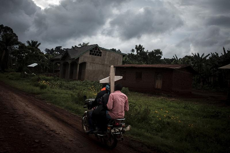 Toll: Three people on a motorbike carry a cross for a grave in Ebola-hit North Kivu