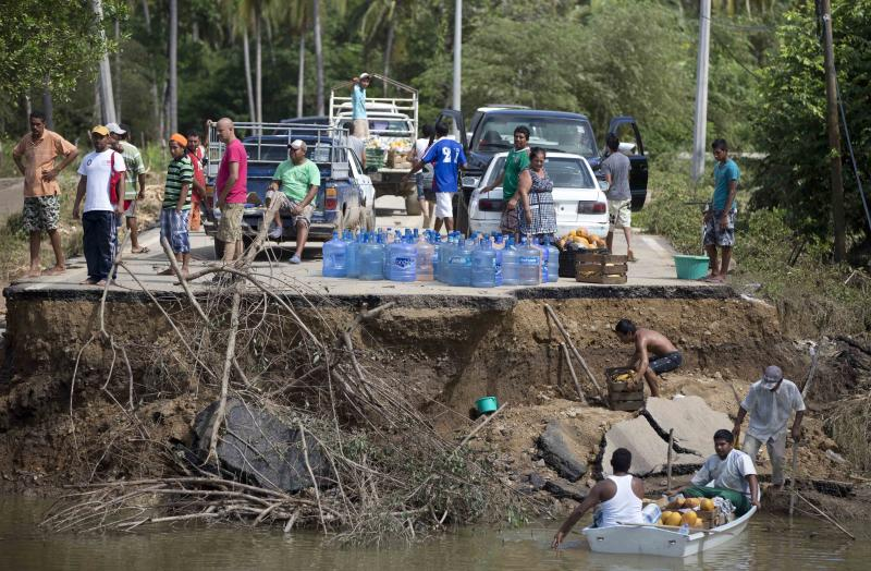 People stand on the edge of a collapsed bridge as they wait to ferry their goods via a boat across the Papagayos River, south of Acapulco, near Lomas de Chapultepec, Mexico, Wednesday, Sept. 18, 2013. Mexico was hit by the one-two punch of twin storms over the weekend, and Tropical Storm Manuel, the storm that soaked Acapulco on Sunday, re-formed into a tropical storm Wednesday, threatening to bring more flooding to the country's northern coast. With roads blocked by landslides, rockslides, floods and collapsed bridges, Acapulco was cut off from road transport. (AP Photo/Eduardo Verdugo)