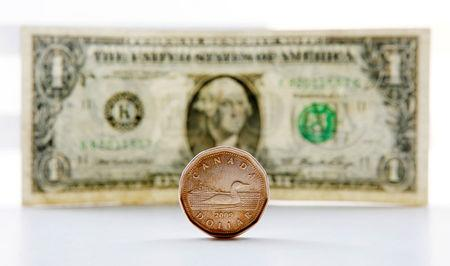 "FILE PHOTO: A Canadian dollar coin, commonly called a ""Loonie"" and an American dollar bill are seen in this staged photo in Toronto"