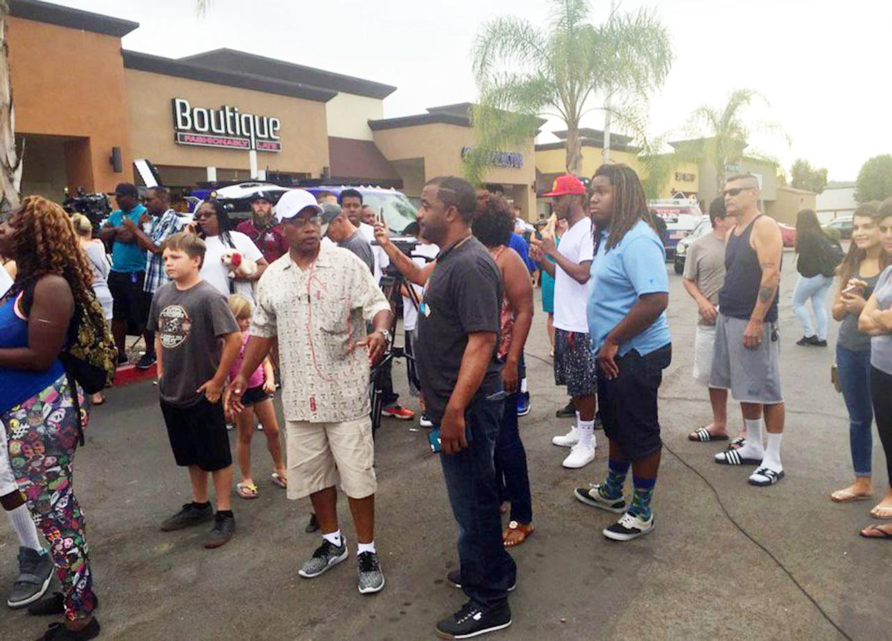 This still from video provided by 10News.com shows people standing near where police shot and wounded a man in the San Diego suburb of El Cajon, Calif., Thursday, Sept. 27, 2016. Police were called to the parking lot of the Broadway Village Shopping Center shortly after 2 p.m. on a call about a man acting erratically. One officer apparently shot the man, who was taken to a hospital. There's no word on his condition. (10News.com via AP)