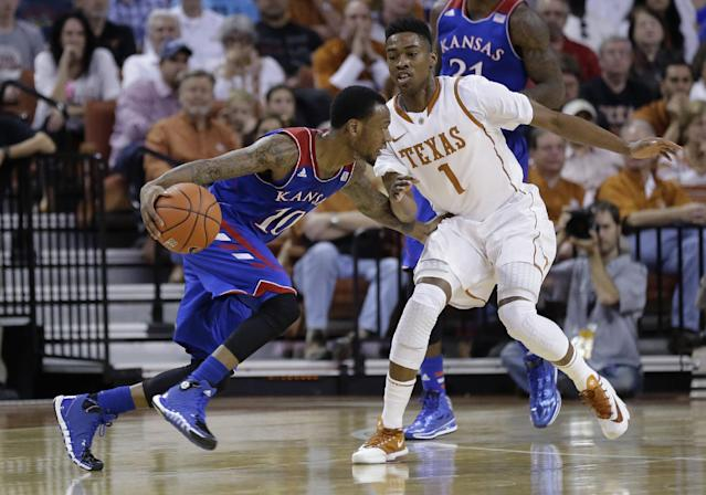 Kansas' Naadir Tharpe (10) looks to get past Texas' Isaiah Taylor (1) during the first half of an NCAA college basketball game, Saturday, Feb. 1, 2014, in Austin, Texas. (AP Photo/Eric Gay)
