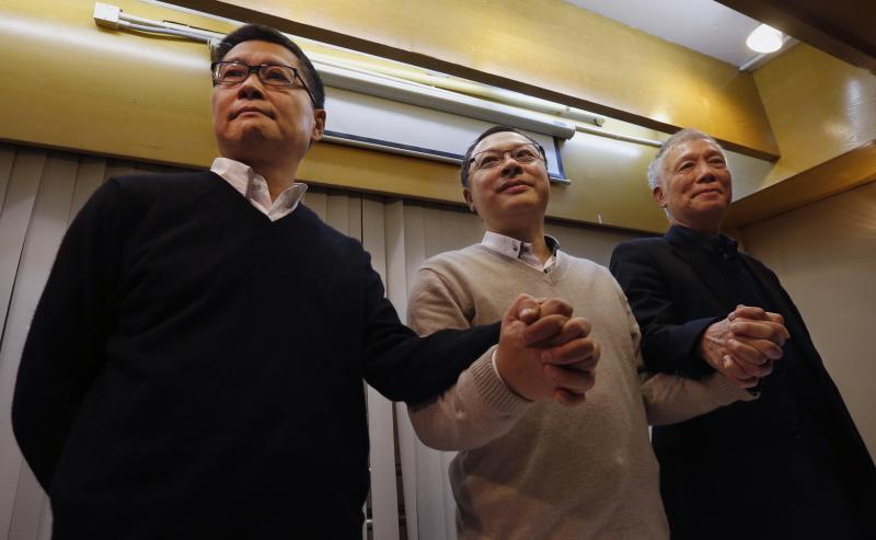 Occupy Central civil disobedience founder Benny Tai (C), a law professor at the University of Hong Kong, along with co-founders Chan Kin-man (L), a professor of sociology at Chinese University and Reverend Chu Yiu-ming, join hands during a news conference on their voluntary surrender to the police in Hong Kong December 2, 2014. The founders of Hong Kong's Occupy Central civil disobedience movement on Tuesday called on pro-democracy activists to pull back from the city's main protest site next to government headquarters and said they will surrender to police.     REUTERS/Bobby Yip  (CHINA - Tags: POLITICS BUSINESS EDUCATION CRIME LAW TPX IMAGES OF THE DAY)