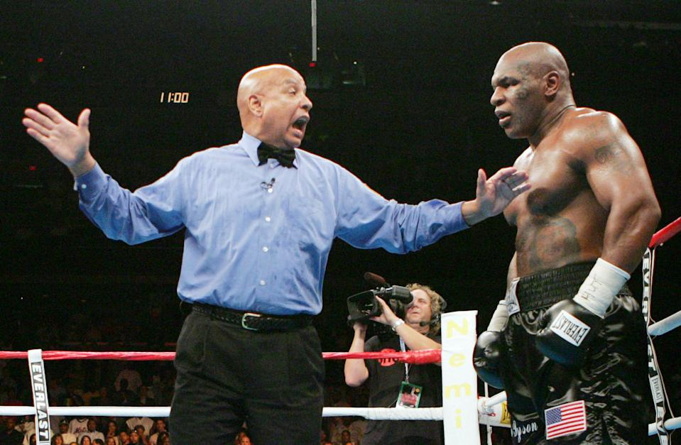 Referee Joe Cortez calls a temporary halt in the fight as he penalizes Mike Tyson two points for head butting Kevin McBride in the sixth round Saturday night, June 11, 2005, at the MCI Center in Washington.   Tyson was pushed to the mat at the end of the round by McBride and didn't answer the bell for the next: giving McBride the win (AP Photo/Pablo Martinez Monsivais)