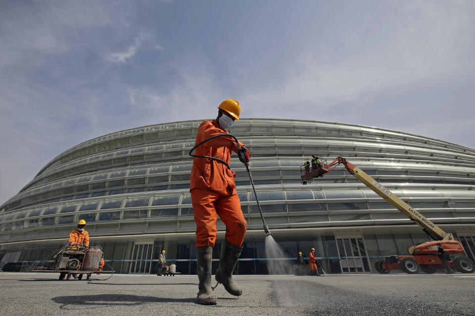 FILE - In this March 31, 2021, file photo, workers fix the surface of a road outside the newly completed National Speed Skating Oval ahead of the 2022 Beijing Winter Olympics test events in Beijing. Beijing organizers on Monday, Oct. 4, 2021 announced a series of new test events. This schedule comes days after organizers and the IOC published rigid restrictions at the Games for athletes and everyone else, controls that apparently have the full support of the IOC. (AP Photo/Andy Wong, File)