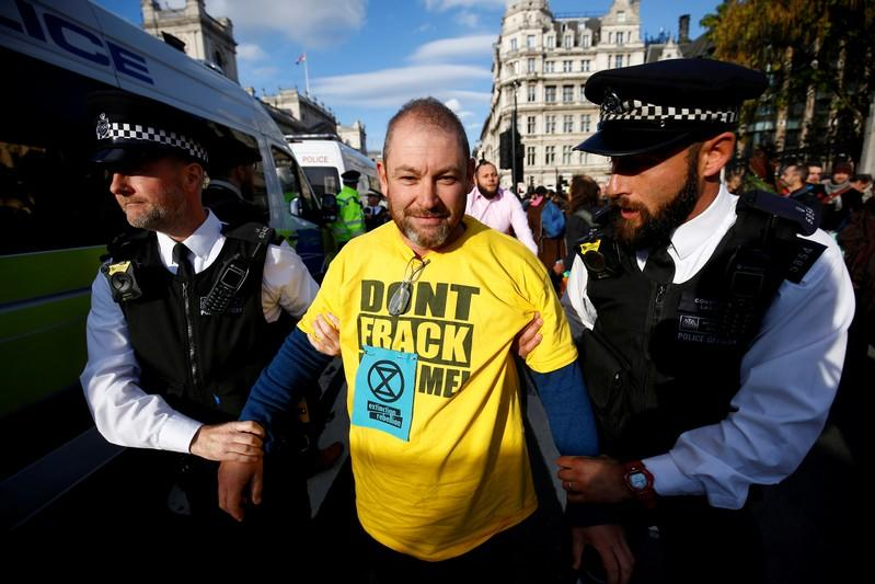 FILE PHOTO: Police officers detain a protester outside the Houses of Parliament during a demonstration against fracking, in London