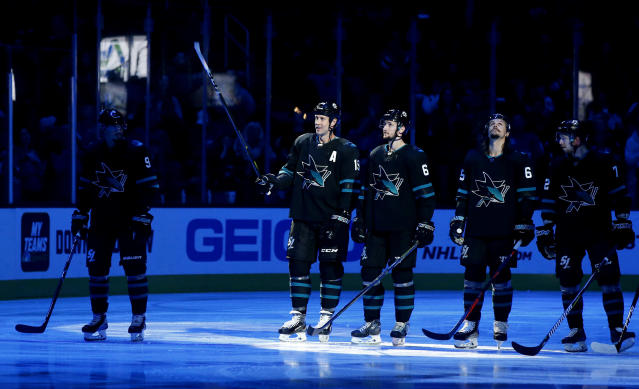 San Jose Sharks' Joe Thornton (19) is honored before the team's NHL hockey game against the Vancouver Canucks, for his 400th goal, 1,000th assist and 1,500th game, in San Jose, Calif., Friday, Nov. 23, 2018. With him are teammates Kevin Lebanc (62) and Erik Karlsson (65). (AP Photo/Josie Lepe)