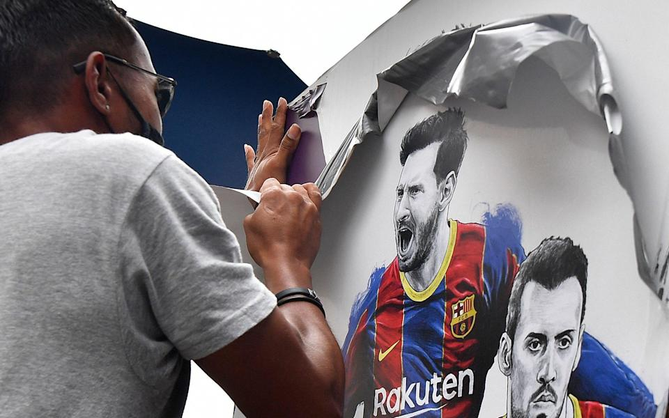 A worker removes posters featuring Barcelona's departing Argentinian forward Lionel Messi at the Camp Nou stadium in Barcelona on August 10, 2021. - France is waiting impatiently for Lionel Messi with supporters gathering outside Paris Saint-Germain's ground hoping to see the Argentine who is expected to join the Qatar-owned club after his exit from Barcelona - AFP
