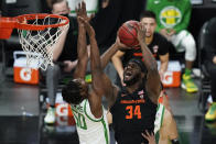 Oregon State's Rodrigue Andela (34) shoots over Oregon's Eric Williams Jr. (50) during the first half of an NCAA college basketball game in the semifinal round of the Pac-12 men's tournament Friday, March 12, 2021, in Las Vegas. (AP Photo/John Locher)