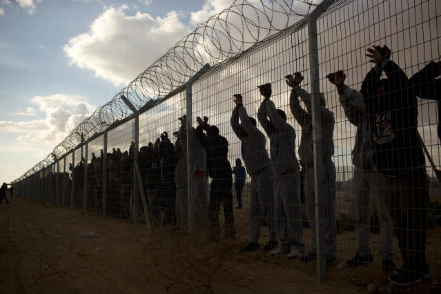 <p>African migrants stand inside Holot detention center as others protest outside it near Ktsiot the Negev Desert in southern Israel, Feb. 17, 2014. (Photo: Oded Balilty/AP) </p>