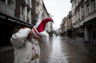 A man wearing a carnival cap stands in a deserted street in the old town in Duesseldorf, Germany, Monday, Feb. 15, 2021. Because of the coronavirus pandemic the traditional carnival parades are canceled. (Fabian Strauch/DPA via AP)