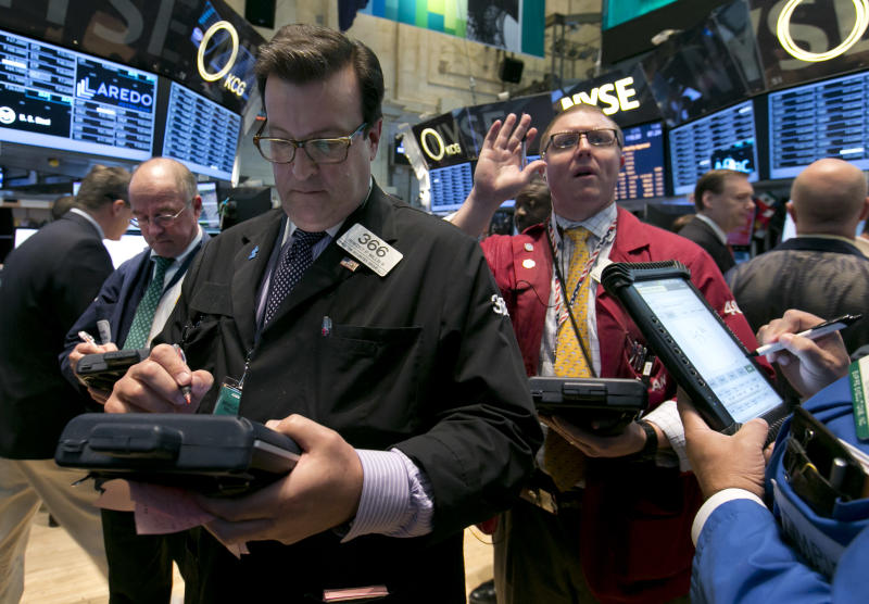 Trader Benedict Willis, foreground left, works on the floor of the New York Stock Exchange, Tuesday, April 22, 2014. Stock futures edged higher as more companies reported first quarter earnings. (AP Photo/Richard Drew)