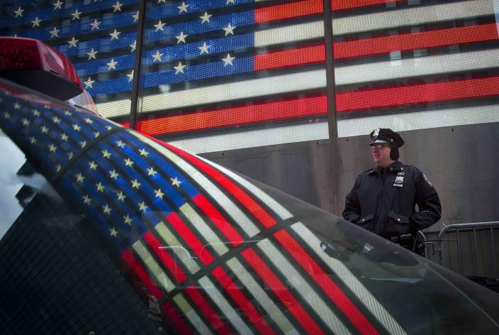 The U.S. flag is reflected in the window of a police car as a police man stands guard in Times Square ahead of New Year's Eve celebrations in New York, December 31, 2013. Security has been stepped up in the area around where the celebrations will take place. REUTERS/Carlo Allegri (UNITED STATES - Tags: SOCIETY TPX IMAGES OF THE DAY)