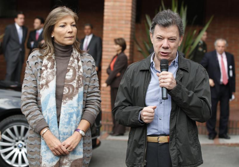 Colombia's President Juan Manuel Santos, accompanied by his wife Maria Clemencia Rodriguez, left, speaks to reporters upon his arrival to the Santa Fe's Clinic Foundation where he will undergo surgery to remove a prostate tumor in Bogota, Colombia, Wednesday, Oct. 3, 2012. (AP Photo/Fernando Vergara)