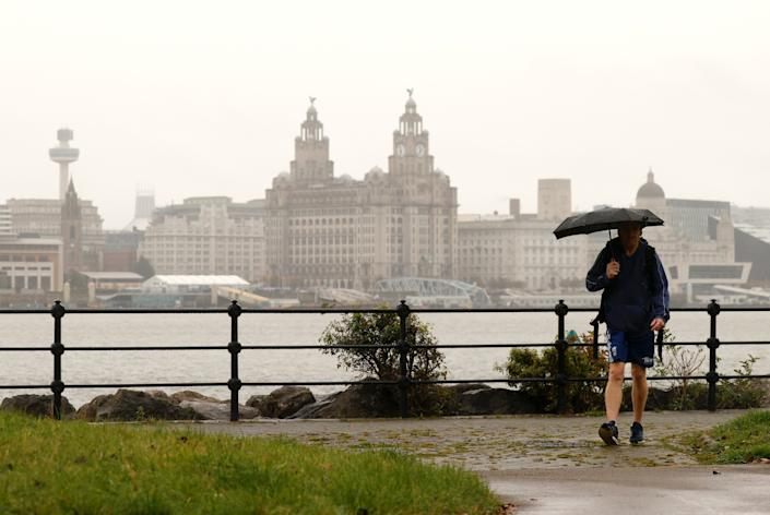 A man holds an umbrella as he walks along the River Mersey with the Liverpool skyline amid the outbreak of the coronavirus disease (COVID-19) in Seacombe, Britain, October 12, 2020. REUTERS/Phil Noble