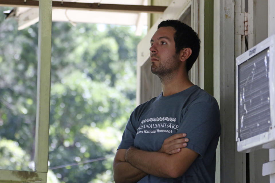 Matt Butschek II, of Dallas, Texas, stands in the doorway of a cabin under quarantine in Honolulu, Thursday, Nov. 5, 2020. Cut off from the rest of the planet since February, Butschek, and three others are re-emerging from Kure Atoll in the Northwestern Hawaiian Islands, one of the most remote places on Earth, into a society changed by the coronavirus outbreak. (AP Photo/Caleb Jones)