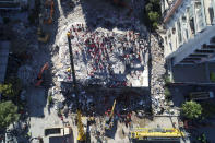 Photo taken with a drone shows rescue workers trying to save residents trapped in debris of a collapsed building, in Izmir, Turkey, Saturday, Oct. 31, 2020. Rescue teams on Saturday ploughed through concrete blocs and debris of eight collapsed buildings in search of survivors of a powerful earthquake that struck Turkey's Aegean coast and north of the Greek island of Samos, leaving unknown numbers of dead and injured. (IHA via AP)