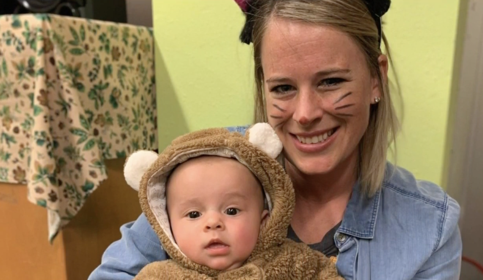 Amanda Zupancic holds a baby while she's dressed in a costume with whiskers.