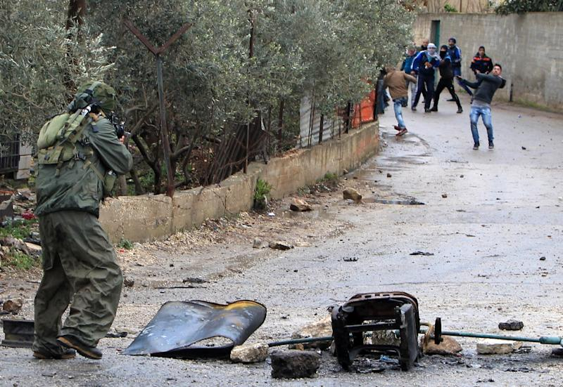 An Israeli soldier aims towards Palestinian prostestors throwing stones during clashes in the village of Qabatiya, near the West Bank town of Jenin, on February 6, 2016 (AFP Photo/Jaafar Ashtiyeh)