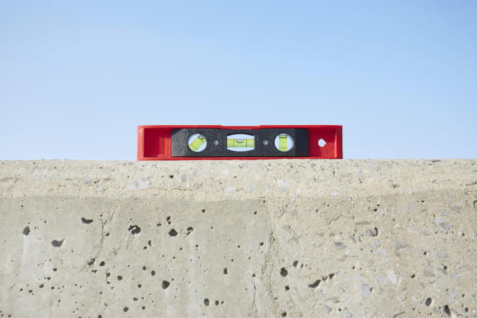 Sill life of red spirit level on concrete wall against blue sky