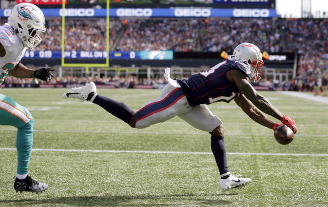 New England Patriots wide receiver Phillip Dorsett makes a fingertip touchdown catch in the end zone in front of Miami Dolphins cornerback Xavien Howard on Sunday. (AP)