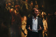 Museum director Taco Dibbits explains how Rembrandt's biggest painting the Night Watch just got bigger with the help of artificial intelligence in Amsterdam, Netherlands, Wednesday, June 23, 2021. Right above Dibbits, left, one of the added parts is seen, the Dutch national museum and art gallery reveals findings from a long-term project to examine in minute detail Rembrandt van Rijn's masterpiece the Night Watch. (AP Photo/Peter Dejong)