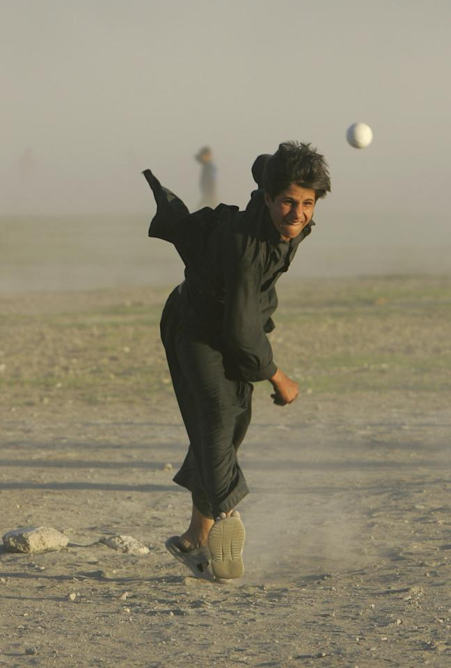 KABUL, AFGHANISTAN - JULY 27:  An Afghan cricket player bowls during a local league game July 27, 2007 in Kabul, Afghanistan. After the fall of the Taliban when the refugees returned from camps in Pakistan they came back having learned a new sport, Cricket. There are now leagues spread across the country playing in dusty fields. For the average Afghan team the equipment is cheap but the uniforms are not affordable so they play in sandals and their traditional shawal kamis. (Photo by Paula Bronstein/Getty Images)