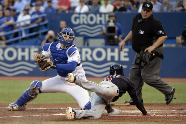 Cleveland Indians left fielder Greg Allen (1) is safe at home as Toronto Blue Jays catcher Danny Jansen (9) is late on the tag during fifth inning of a baseball game, Wednesday, July 24, 2019 in Toronto. (Nathan Denette/Canadian Press via AP)