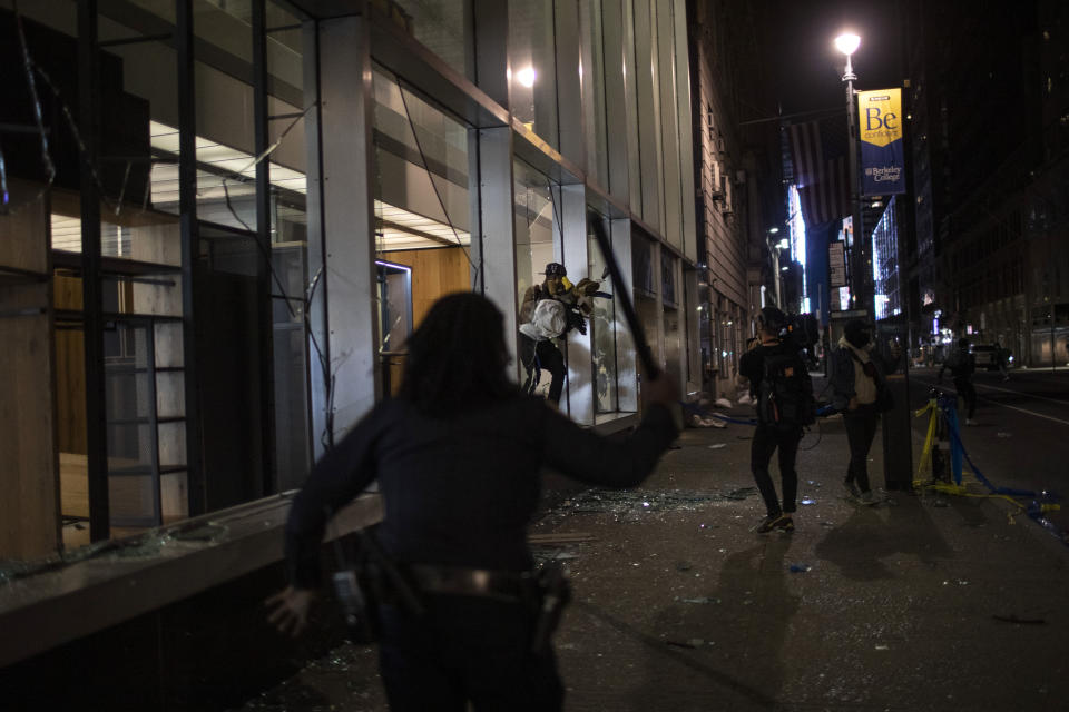 Police run towards people as they jump out of a store with items they took hours after a solidarity rally calling for justice over the death of George Floyd Monday, June 1, 2020, in New York. Floyd died after being restrained by Minneapolis police officers on May 25. (AP Photo/Wong Maye-E)