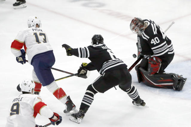 Chicago Blackhawks goaltender Robin Lehner makes a save on a backhand shot by Florida Panthers' Mark Pysyk (13) as Olli Maatta also defends during the first period of an NHL hockey game Tuesday, Jan. 21, 2020, in Chicago. (AP Photo/Charles Rex Arbogast)