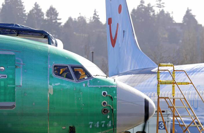 """FILE- In this March 13, 2019, file photo people work in the flight deck of a Boeing 737 MAX 8 airplane being built for TUI Group parked next to another MAX 8 also designated for TUI at Boeing Co.'s Renton Assembly Plant in Renton, Wash. U.S. prosecutors are looking into the development of Boeing's 737 Max jets, a person briefed on the matter revealed Monday, the same day French aviation investigators concluded there were """"clear similarities"""" in the crash of an Ethiopian Airlines Max 8 last week and a Lion Air jet in October. (AP Photo/Ted S. Warren, file)"""