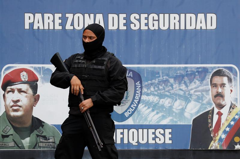 A member of the Bolivarian National Intelligence Service (SEBIN) stands guard, outside a detention center, where a riot occurred, according to relatives, in Caracas