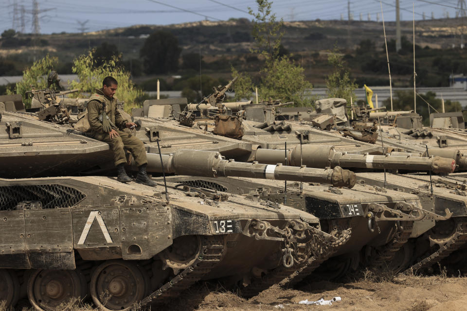 An Israeli soldier sits on top of a tank at a staging ground near the border with Gaza Strip, southern Israel, Friday, May 21, 2021. A cease-fire took effect early Friday after 11 days of heavy fighting between Israel and Gaza's militant Hamas rulers that was ignited by protests and clashes in Jerusalem. (AP Photo/Tsafrir Abayov)