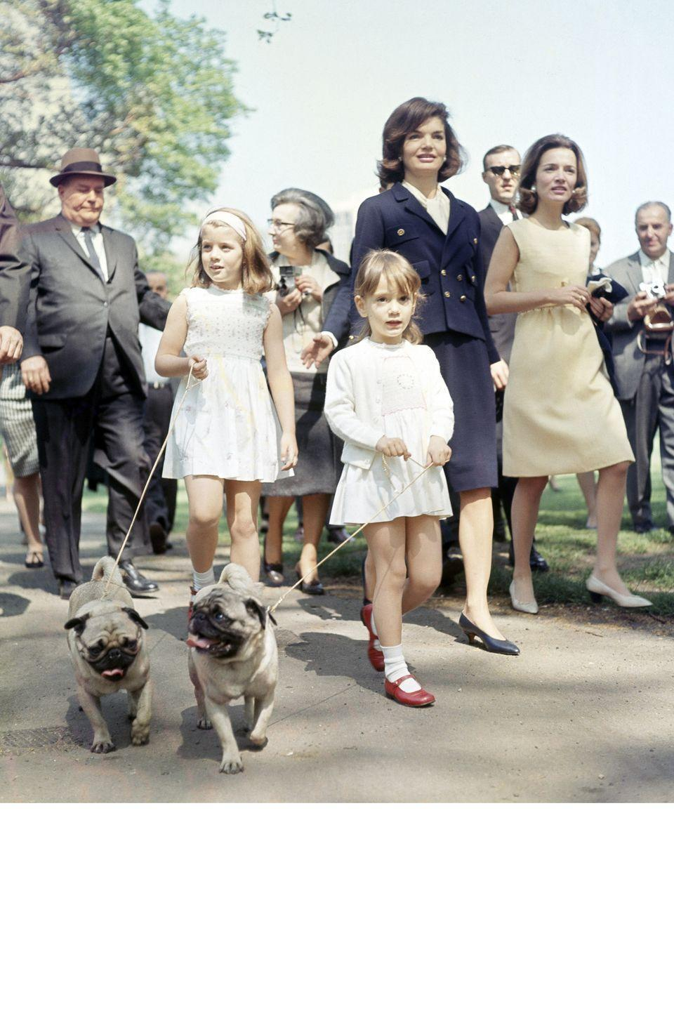 <p>Always a chic pair, the former First Lady is captured walking with her sister Princess Lee Radziwill in a nautical-inspired navy suit with gold buttons. Daughter Caroline and niece Anna opted for mini dresses. </p>