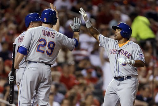 New York Mets' Marlon Byrd, right, is congratulated by teammates John Buck, left, and Ike Davis (29) after hitting a two-run home run during the sixth inning of a baseball game against the St. Louis Cardinals on Tuesday, May 14, 2013, in St. Louis. (AP Photo/Jeff Roberson)