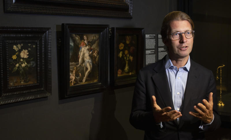 "Rijksmuseum director Taco Dibbits, standing in front of Bartholomeus Spanger's ""Body of Christ Supported by Angels"" oil on copper painting, center, discusses the gift of the major painting the cultural institution received to underscore support for the victims of the coronavirus pandemic and the crisis that museums face world wide, which went on display in Amsterdam, Netherlands, Monday, June 1, 2020. The Dutch government took a major step to relax the coronavirus lockdown, with bars, restaurants, cinemas and museums reopening under strict conditions. (AP Photo/Peter Dejong)"