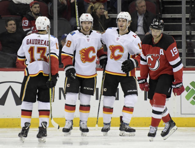 Calgary Flames center Elias Lindholm (28) celebrates his goal with Johnny Gaudreau (13) and Matthew Tkachuk as New Jersey Devils center Travis Zajac, right, reacts during the second period of an NHL hockey game Wednesday, Feb. 27, 2019, in Newark, N.J. (AP Photo/Bill Kostroun)