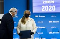 Ella Pamfilova, head of Russian Central Election Commission, wearing a face mask and gloves to protect against coronavirus, speaks to a member of the Central Election Commission after her news conference in Moscow, Russia, Thursday, July 2, 2020. Almost 78% of voters in Russia have approved amendments to the country's constitution that will allow President Vladimir Putin to stay in power until 2036, Russian election officials said Thursday after all the votes were counted. Kremlin critics said the vote was rigged. (AP Photo/Alexander Zemlianichenko)
