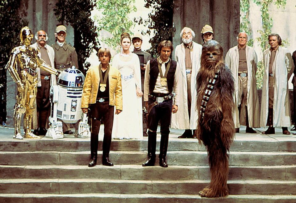 """Kenny Baker (R2-D2), Mark Hamill, Carrie Fisher, Harrison Ford, Peter Mayhew (Chewbacca) in the original """"Star Wars."""" (Photo: 20th Century Fox/Lucasfilm courtesy of the Everett Collection.)"""